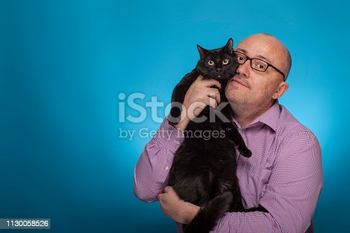 istock A businessman in a piked shirt holds  a black cat in the hand,  on the blue background. 1130058526