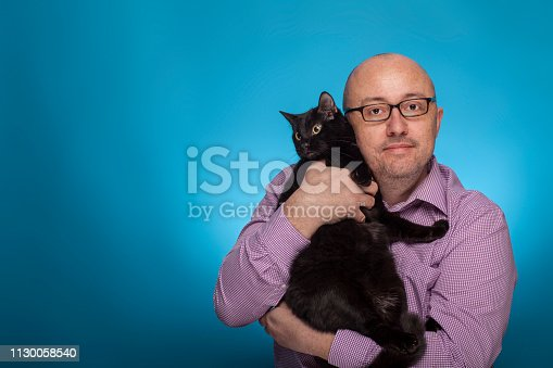 istock A businessman in a piked shirt holds  a black cat in the hand,  on the blue background. 1130058540