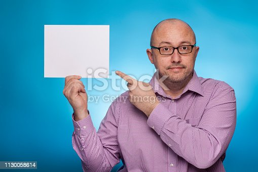 istock A businessman in a piked shirt holds a blank, white sign,  placeholder,  on the blue background. 1130058614