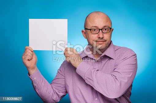 istock A businessman in a piked shirt holds a blank, white sign,  placeholder,  on the blue background. 1130058627
