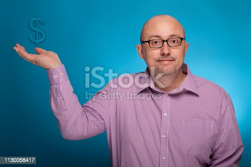 istock A businessman in a piked shirt holds a dollar sign in the hand,  on the blue background. 1130058417