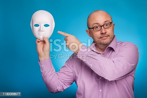 istock A businessman in a piked shirt holds a white mask, second face in his hand,  on the blue background. 1130058577