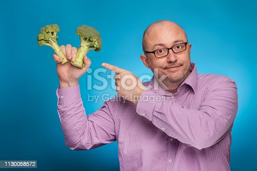 istock A businessman in a piked shirt holds broccoli in hand,  on the blue background. 1130058572