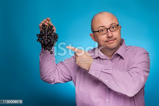 istock A businessman in a piked shirt holds grapes in hand,  on the blue background. 1130058576