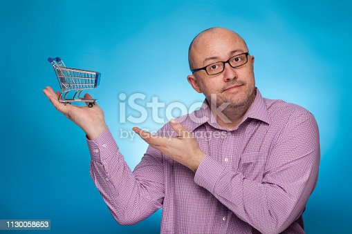istock A businessman in a piked shirt pointing with the hand on a shopping cart,  on the blue background. 1130058653