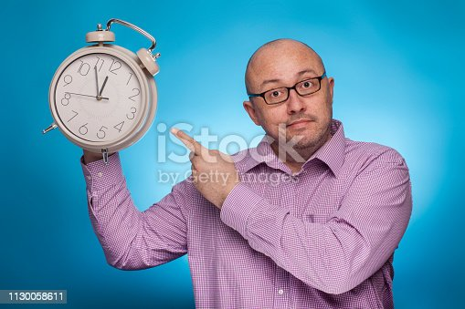 istock A businessman in a piked shirt pointing with the index finger on a huge alarm clock,  on the blue background. 1130058611