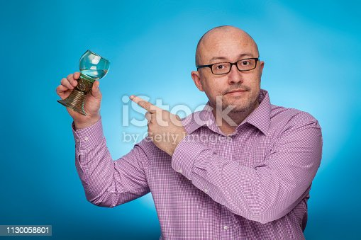 istock A businessman in a piked shirt pointing with the index finger on a antique glass of wine,  on the blue background. 1130058601