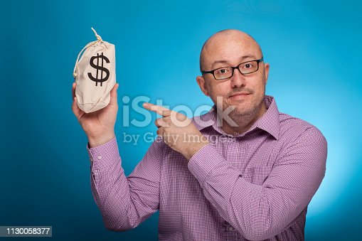 istock A businessman in a piked shirt pointing with the index finger on a sack with dollars,  on the blue background. 1130058377