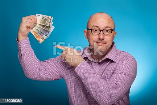 istock A businessman in a piked shirt pointing with the index finger  on euro cash,  on the blue background. 1130058389