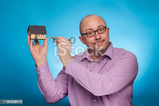 istock A businessman in a piked shirt with a house and apartment key,  on the blue background. 1130058579