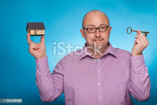 istock A businessman in a piked shirt with a house and apartment key,  on the blue background. 1130058586