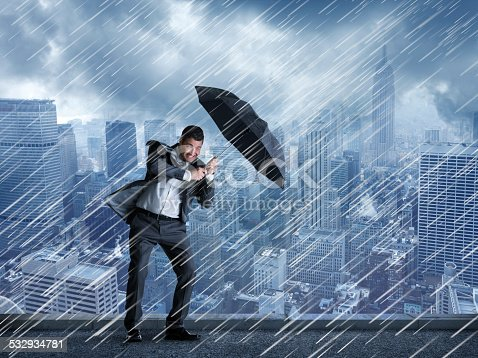 A businessman holding an umbrella during a rainstorm with a big city skyline in the background.