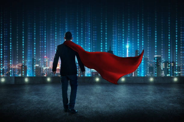 Businessman in a suit and cape hero standing on rooftop with virtual modern city skyline . stock photo