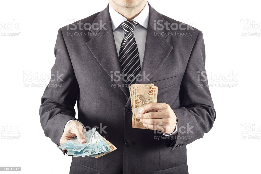businessman in a suit giving brazilian money stock photo