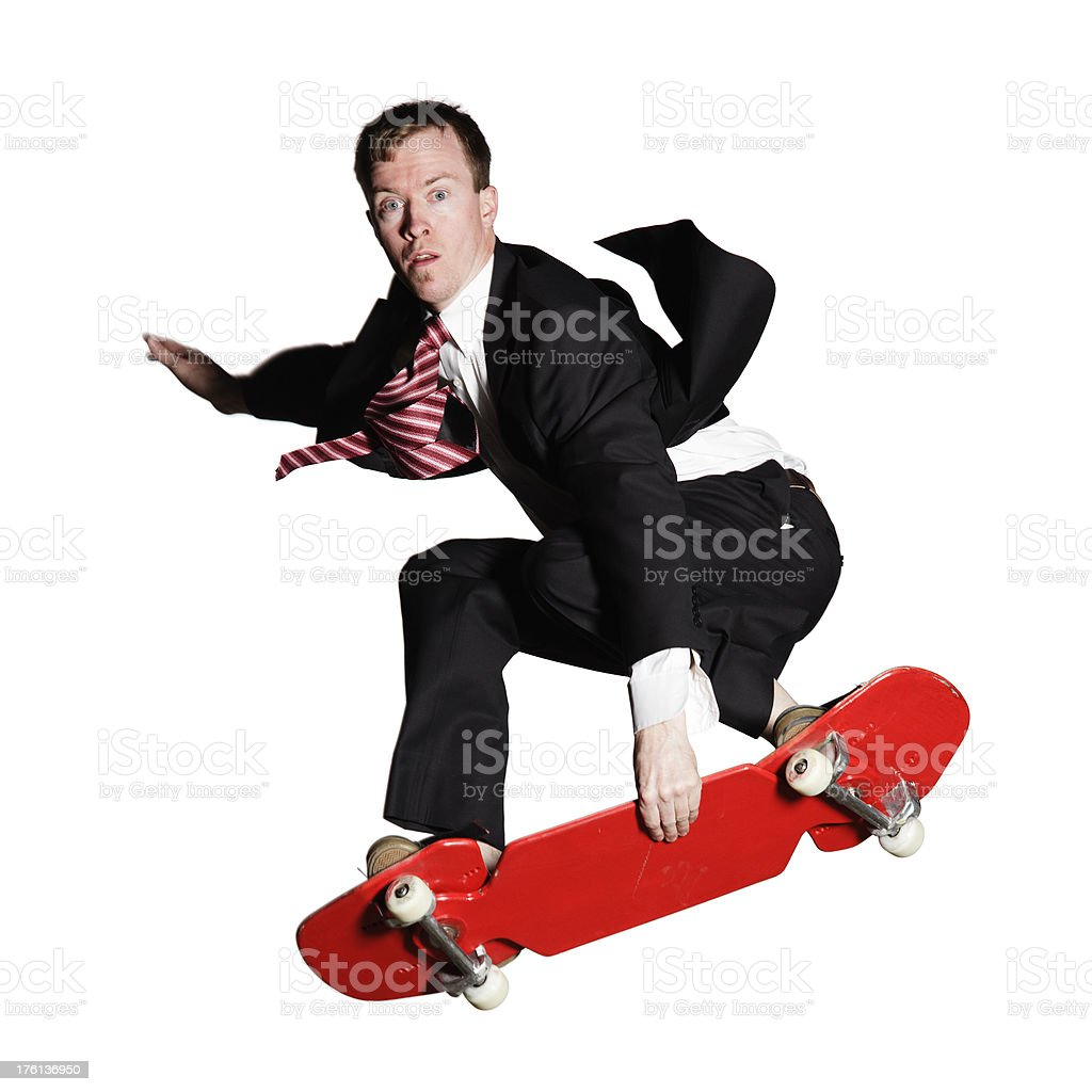 Businessman in a suit showing off skateboarding, isolated on white royalty-free stock photo