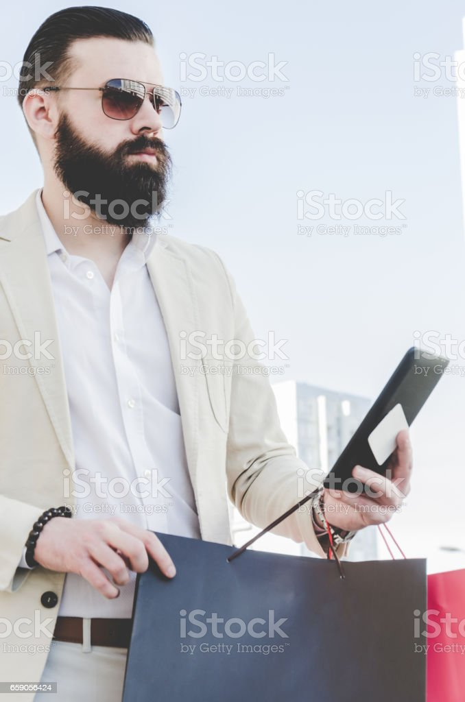 businessman in a suit with a long beard holding shopping bags and credit card royalty-free stock photo