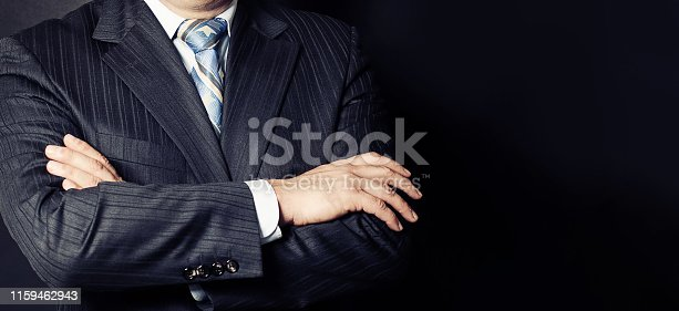 Businessman in a suit with his hands arms crossed on black background