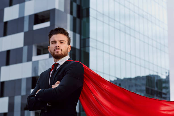 Businessman in a superhero costume against a business building b stock photo