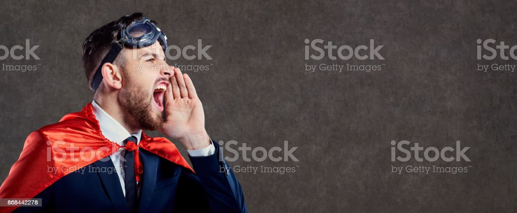 A businessman in a superhero costume calls screams. stock photo
