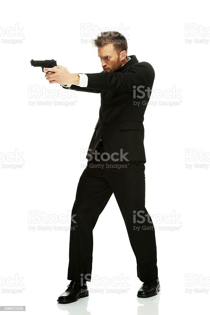 Businessman in action with handgun stock photo