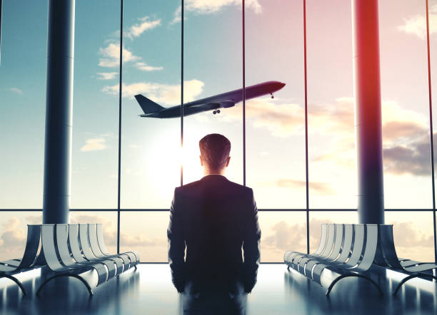 Businessman in airport and looking at airplane stock photo