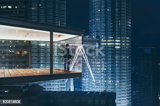 istock Businessman in an modern sky office by night with beautiful city skyline view . 820819806