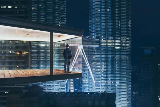 geschäftsmann in einem modernen himmel büro bei nacht mit blick auf die schöne stadt skyline. - fensterfront stock-fotos und bilder