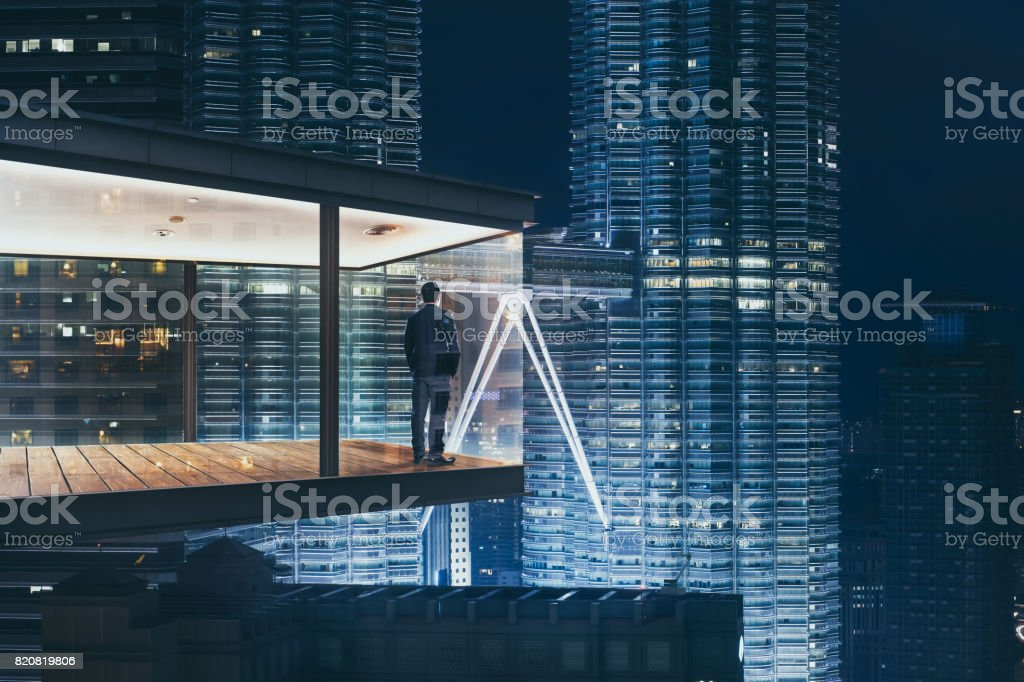 Geschäftsmann in einem modernen Himmel Büro bei Nacht mit Blick auf die schöne Stadt Skyline. – Foto