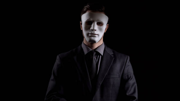 Businessman in anonymous mask looking at camera, corruption schemes, fraud Businessman in anonymous mask looking at camera, corruption schemes, fraud individual event stock pictures, royalty-free photos & images