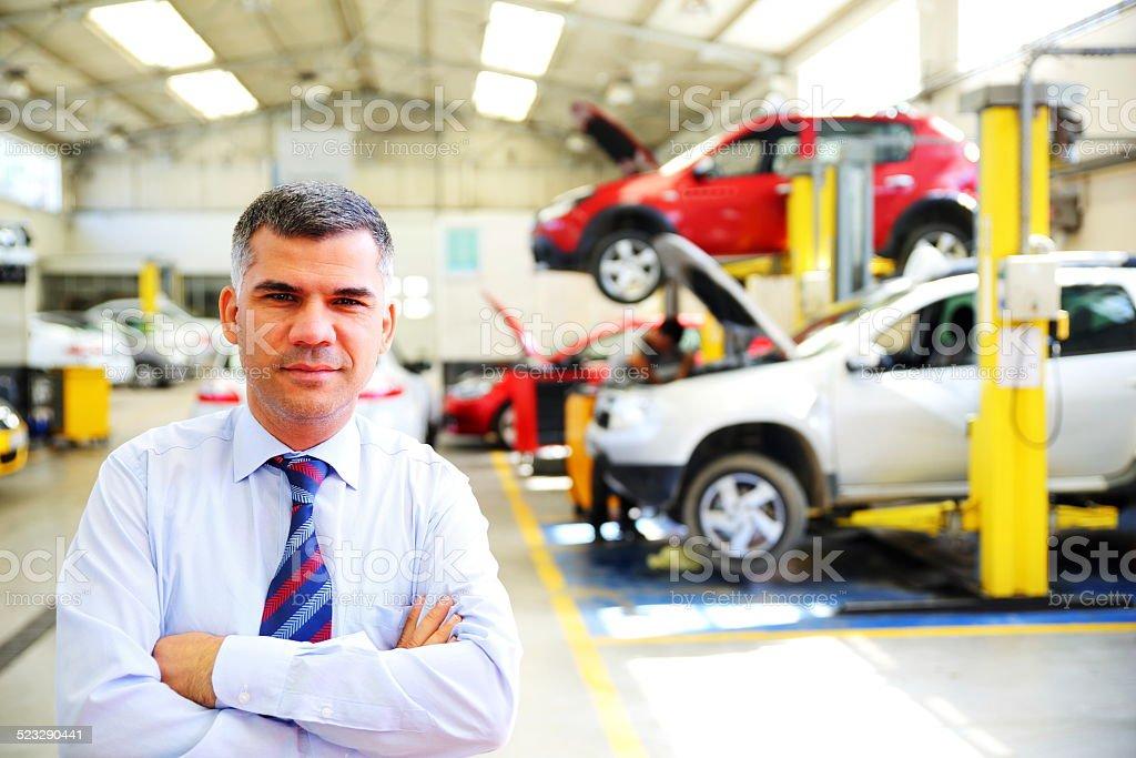 Businessman in Auto repair shop stock photo