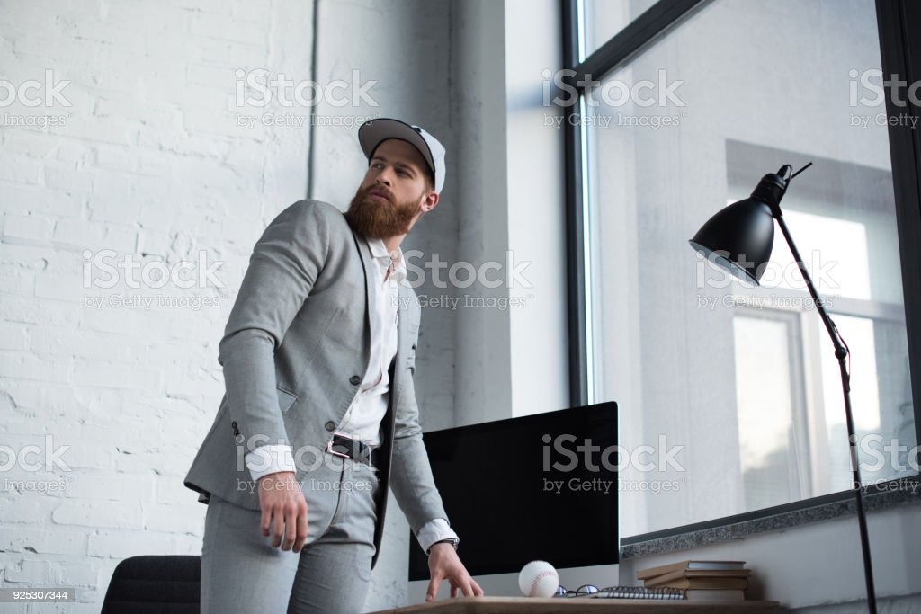 businessman in baseball cap looking away in office stock photo