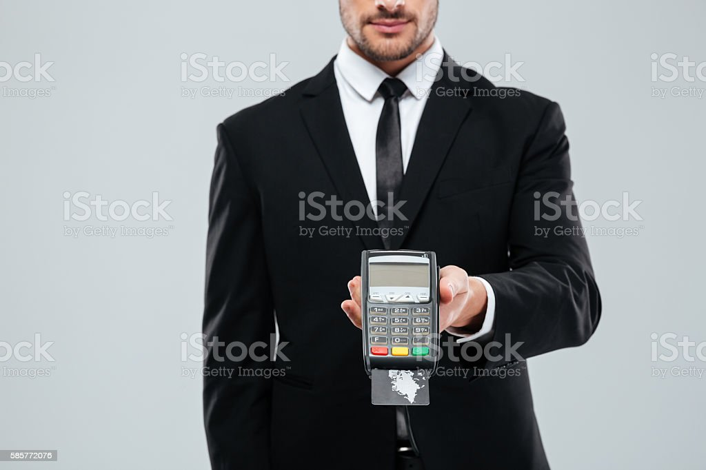 Businessman in black suit holding bank terminal with credit card stock photo