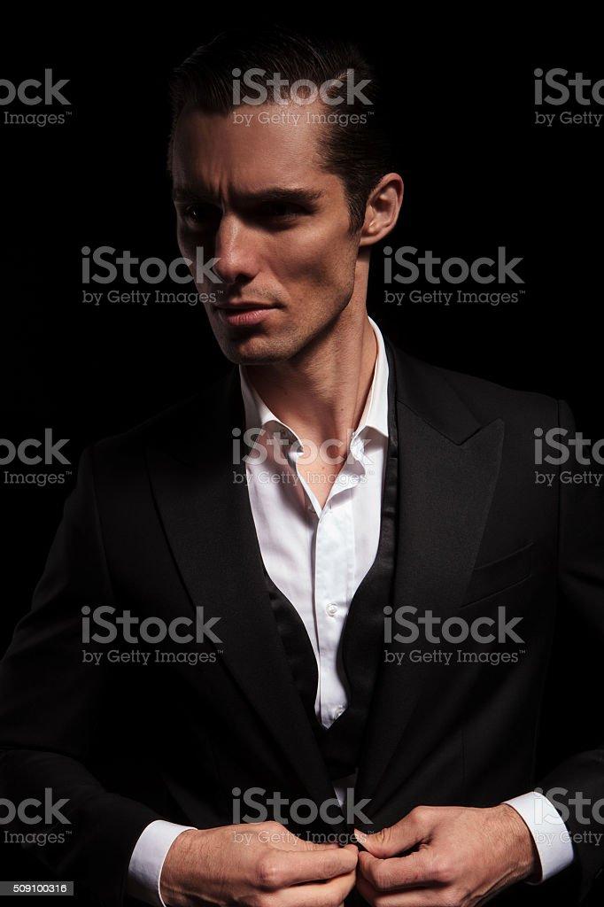 businessman in black suit in dark studio closing his jacket stock photo