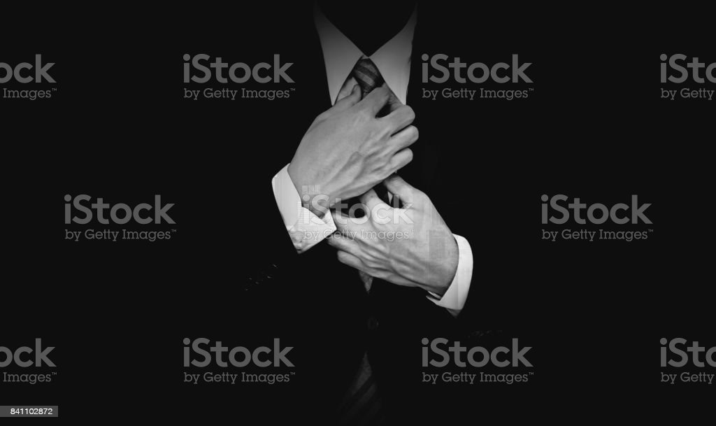 Businessman in black suit on black background, black and white stock photo