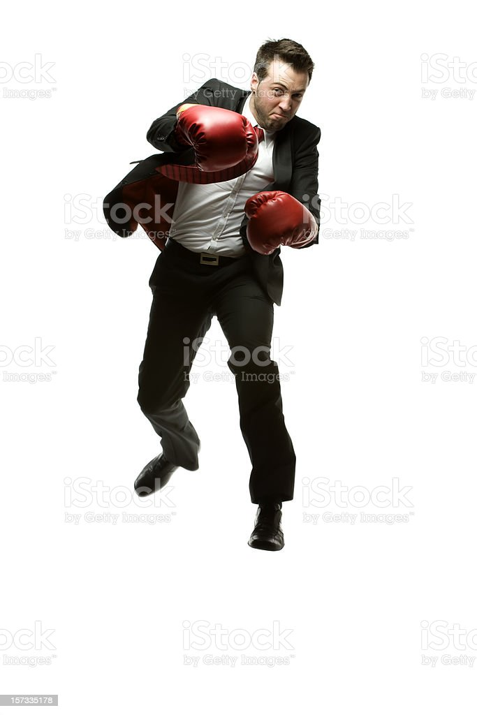 Businessman in black suit punching with red gloves stock photo