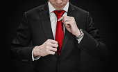 Businessman in black suit tying red necktie on black background