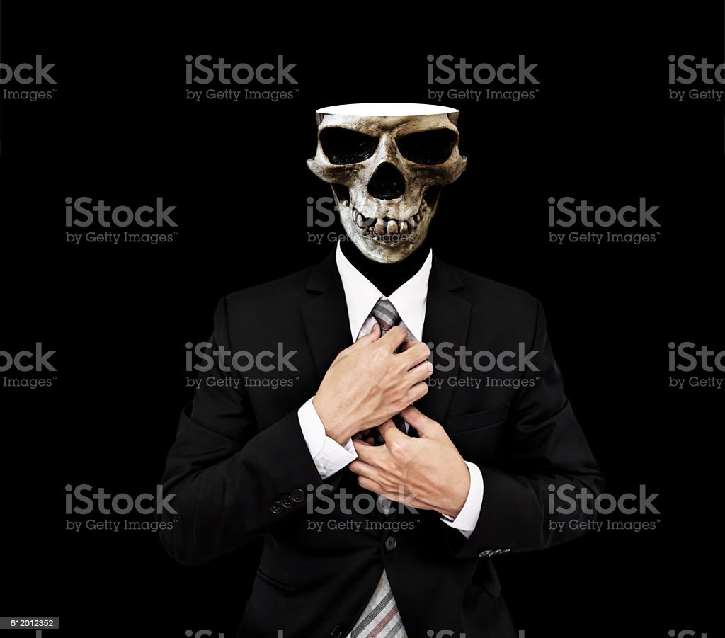 Businessman in black suit with ckull opening, on black background stock photo