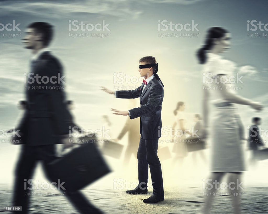 Businessman in blindfold among group of people stock photo