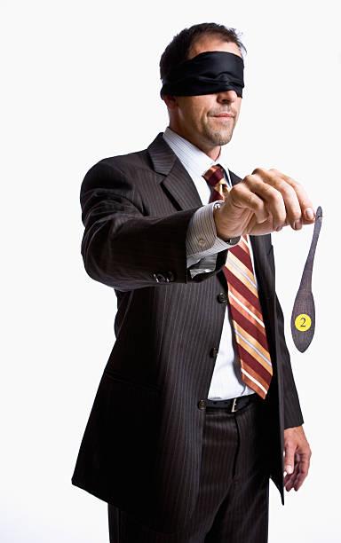 Businessman in Blindfold Holding Donkey Tail stock photo