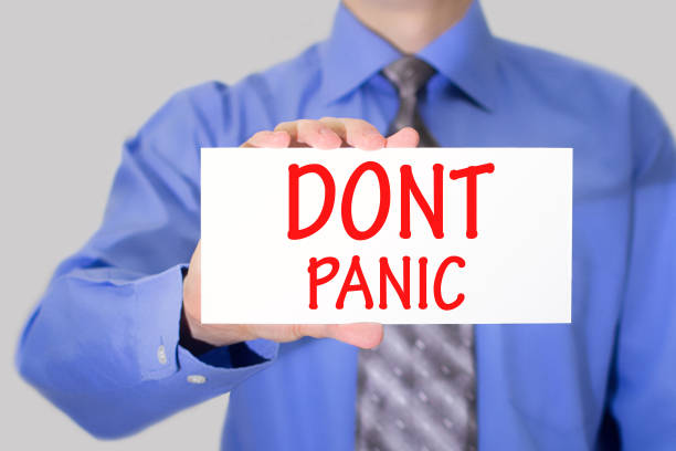 Businessman in blue shirt and gray tie shows a card with the inscription dont panic stock photo