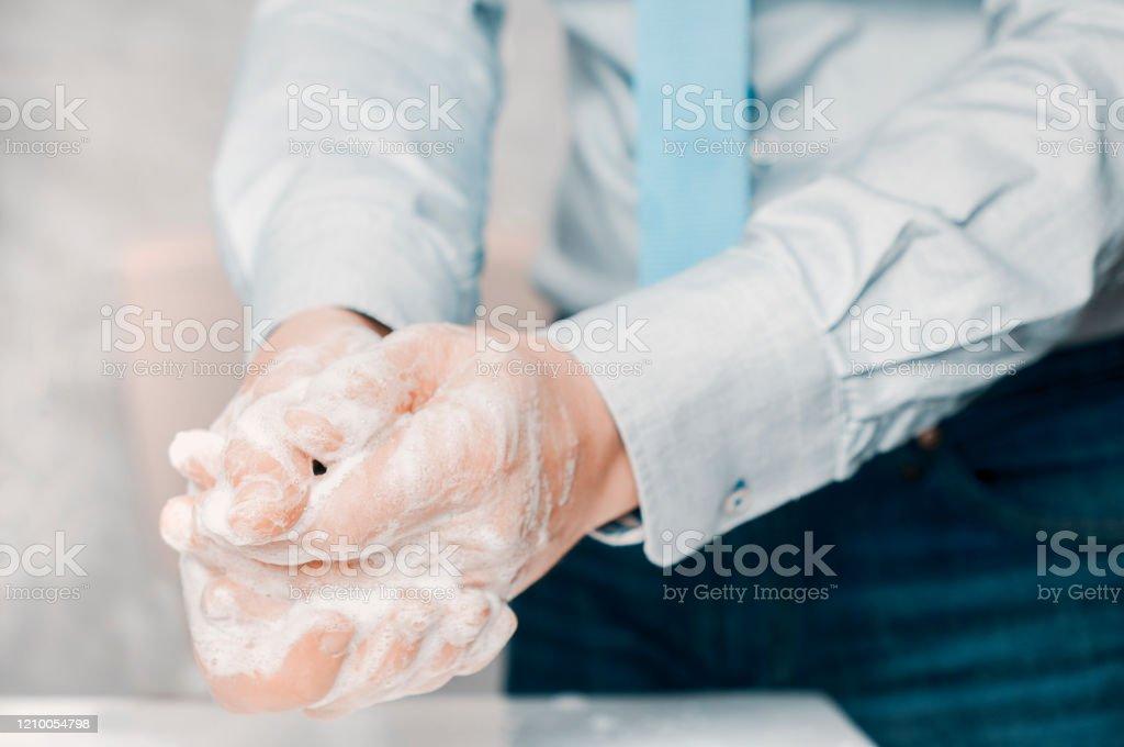 Empresário de camisa azul e gravata lava as mãos profundamente. A lavagem das mãos é muito importante para evitar o risco de contágio de coronavírus e bactérias. - Foto de stock de Adulto royalty-free