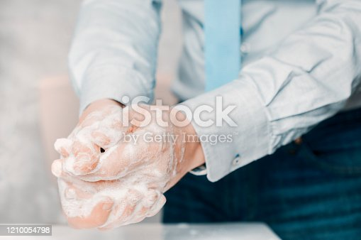 Businessman in blue shirt and tie wash his hands deeply. Hand washing is very important to avoid the risk of contagion from coronavirus and bacteria.