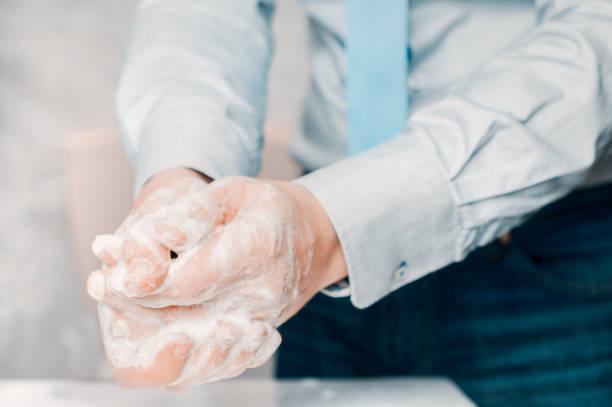 empresário de camisa azul e gravata lava as mãos profundamente. a lavagem das mãos é muito importante para evitar o risco de contágio de coronavírus e bactérias. - washing hands - fotografias e filmes do acervo
