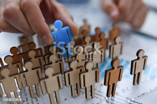 A businessman in blue shirt is holding object in his hand, is searching for personnel or people. Detective looking for missing person crowd of miniature figures choosing most suitable one