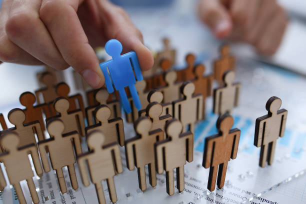 A businessman in blue shirt is holding a magnifying A businessman in blue shirt is holding object in his hand, is searching for personnel or people. Detective looking for missing person crowd of miniature figures choosing most suitable one aptitude stock pictures, royalty-free photos & images