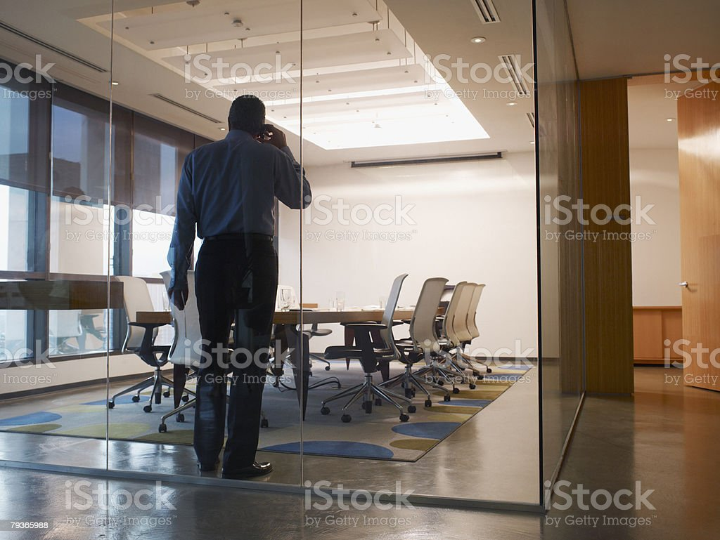 Businessman in boardroom on his mobile phone 免版稅 stock photo