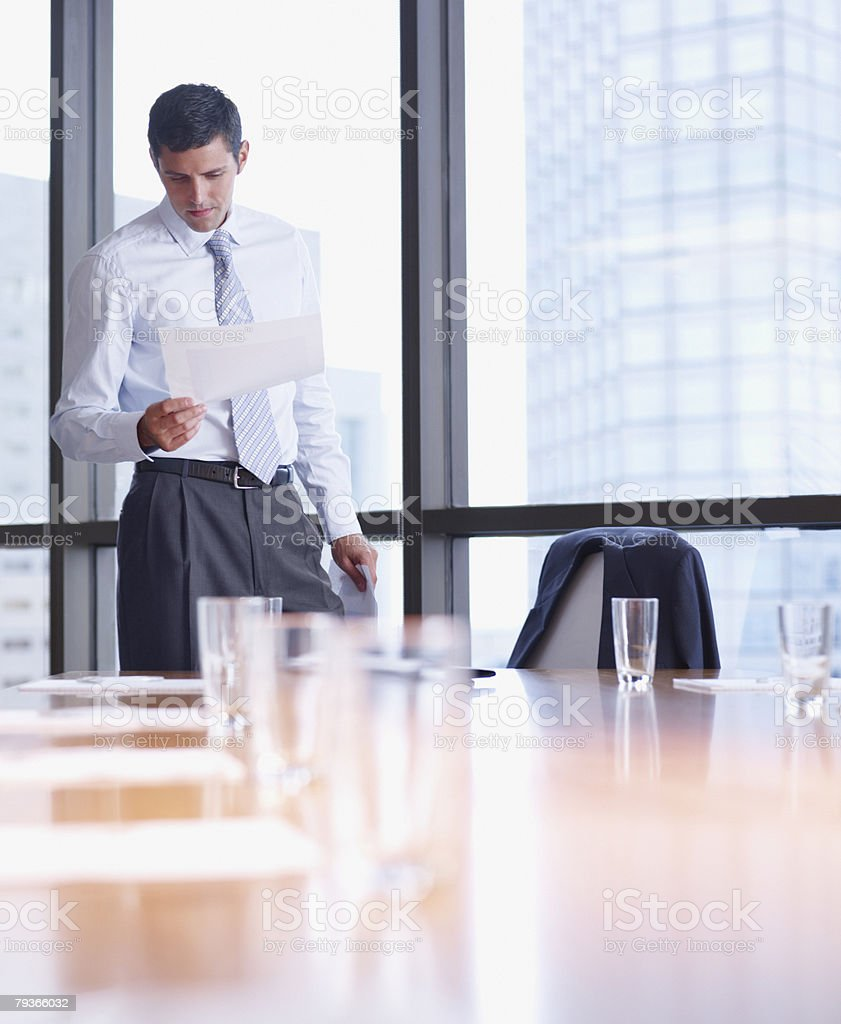 Businessman in boardroom with paperwork by large windows royalty-free stock photo
