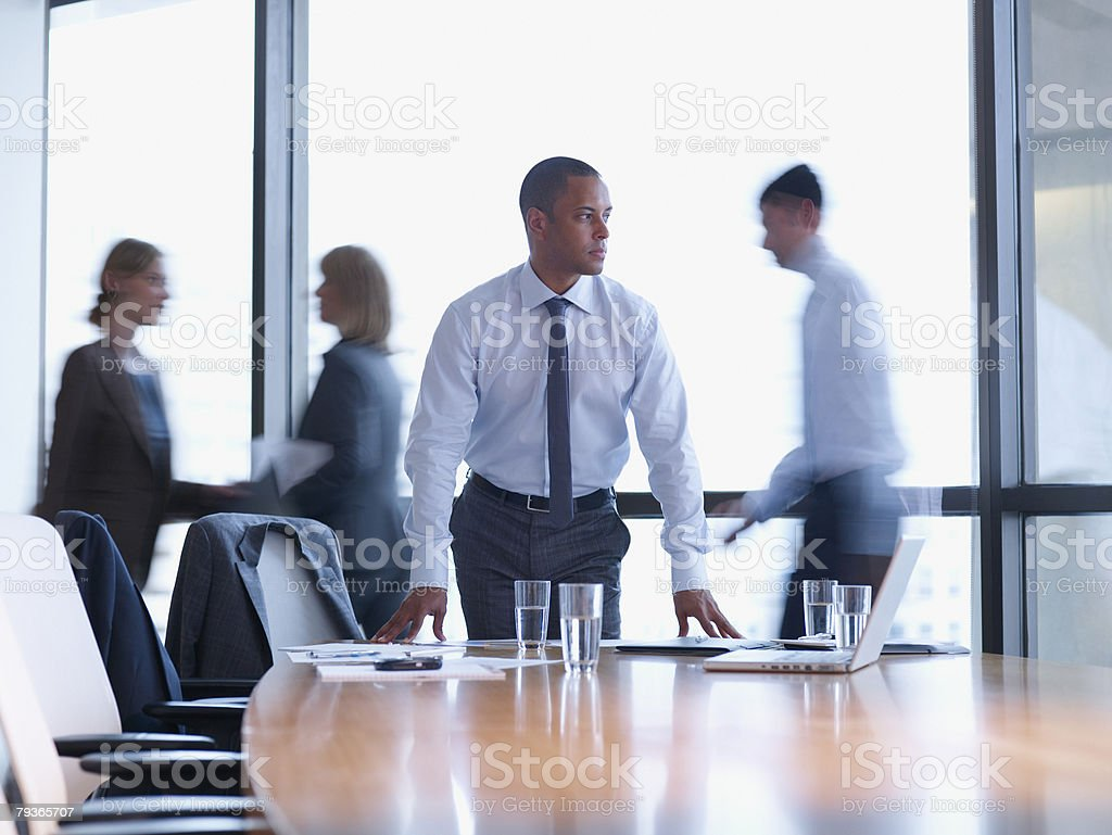 Businessman in boardroom with three co-workers behind him stock photo