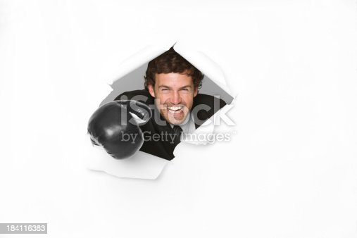 160558362 istock photo Businessman in boxing gloves emerging through a hole 184116383