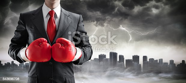 istock Businessman In Boxing Gloves With Cityscape In Storm 543696708